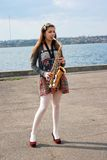 Beautiful girl with saxophone Stock Images