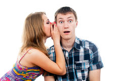 Beautiful girl says a guy whispers in your ear royalty free stock photography