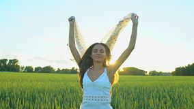 Beautiful girl with scarf flying in wind running on wheat field in sunset. Freedom beayty health happiness concept. Happy young woman in field with long hair stock footage