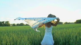 Beautiful girl with scarf flying in wind running on wheat field in sunset. Freedom beayty health happiness concept. Happy young woman in field with long hair stock video footage