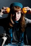 Beautiful girl with scarf and hat and oranges Royalty Free Stock Images