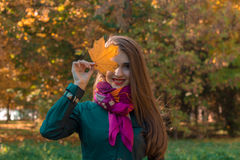 Beautiful girl in scarf keeps autumn leaf near the eyes and smiles Stock Photography