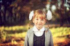 Beautiful girl schoolgirl with bows and smiles Royalty Free Stock Images