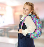Beautiful girl schoolgirl with a satchel on his shoulders. Royalty Free Stock Photos