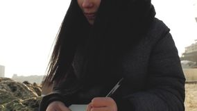 Beautiful girl by the sea in a knitted hat writes with a pen in a notebook.  stock footage