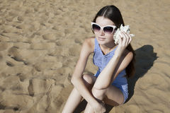 Beautiful girl with a seashell on the beach. Beautiful girl with a seashell sit on the sand. Call to me. Hear the sea Royalty Free Stock Photography