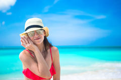 Beautiful girl with seashell in hands at tropical beach Royalty Free Stock Photos