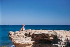 Beautiful girl on the seashore. Beautiful girl posing on the rocky seashore Stock Photo
