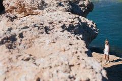 Beautiful girl on the seashore. Beautiful girl posing on the rocky seashore Royalty Free Stock Photography