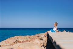 Beautiful girl on the seashore. Beautiful girl posing on the rocky seashore sitting on the bridge Stock Images