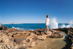 Beautiful girl on the seashore. Beautiful girl posing on the rocky seashore with water splash Stock Photo
