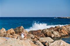 Beautiful girl on the seashore. Beautiful girl posing on the rocky seashore with water splash Stock Image