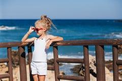 Beautiful girl on the seashore. Beautiful girl in red sunglasses posing on the seashore Royalty Free Stock Image
