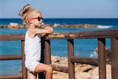 Beautiful girl on the seashore. Beautiful girl in red sunglasses posing on the seashore Stock Image