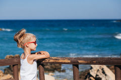 Beautiful girl on the seashore. Beautiful girl in red sunglasses posing on the seashore Stock Photo
