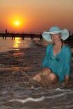 Beautiful girl on the seashore at sunset Royalty Free Stock Image
