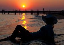 Beautiful girl on the seashore at sunset Stock Photography