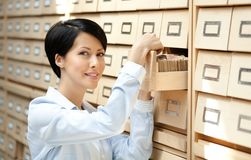 Beautiful girl seeks something in card catalog Royalty Free Stock Photo