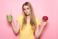 Beautiful girl is selecting between healthy green gluten-free organic smoothie and unhealthy food. Nutrition choice concept. Beautiful girl is selecting between stock photo