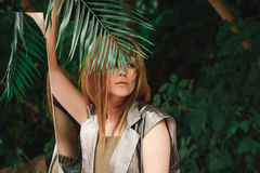 A beautiful girl with a sensual look is covering her eyes with a fern branch stock photos
