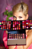 Beautiful girl with set of lipsticks for make-up. Beautiful girl holding a set of colored lipsticks for make-up Stock Photo