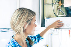 Beautiful Girl Is Seting Up a Boiler Royalty Free Stock Image
