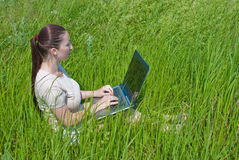 Beautiful girl setting outdoor with laptop summer Stock Image