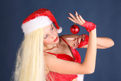 Beautiful girl in sexy New Year suit holds Christmas ball Stock Image