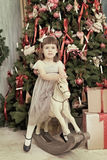 Beautiful girl shakes on a horse rocking chair Royalty Free Stock Image