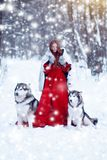 Beautiful girl in sheepskin coat with the dogs. The girl with the siberian husky or wolf or Malamute. Fairy tale girl embracing cute dog in winter park Royalty Free Stock Images
