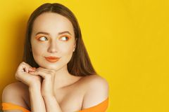 Beautiful girl with shiny brown straight long hair. Woman with orange makeup with freckles. Girl near empty copy space looks away stock images