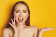 Beautiful girl with shiny brown straight long hair. Woman with orange makeup with freckles. Girl near empty copy space royalty free stock images