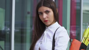 Young girl in a shirt with a bow. Beautiful girl in a shirt with a bamboo bow aiming to the camera against the background of a glass office. Close up stock footage