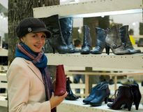 Beautiful girl in a shop. Buying winter boots Royalty Free Stock Photography