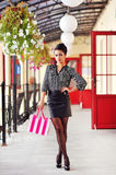 Beautiful girl with shopping bag near retail store. Full length Stock Images
