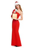 Beautiful girl with shopping bag in red gown and santa hat isolated on white background, christmas holiday concept Royalty Free Stock Photos