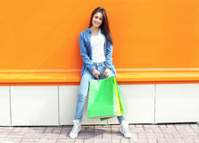Beautiful girl with shopping bags in jeans clothes. Over orange wall Royalty Free Stock Images