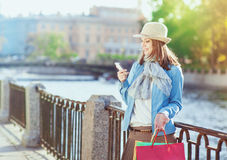 Beautiful girl with shopping bags and mobile phone Royalty Free Stock Photography