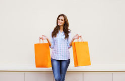 Beautiful girl with shopping bags posing against white wall Royalty Free Stock Images