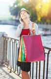 Beautiful girl with shopping bags talking on the mobile Stock Images