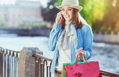 Beautiful girl with shopping bags talking on the mobile Royalty Free Stock Images