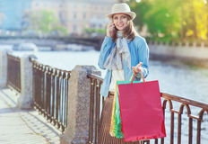 Beautiful girl with shopping bags talking on the mobile Stock Image