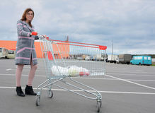 Beautiful girl with a shopping cart products from a supermarket on the background of a shopping center. Royalty Free Stock Images