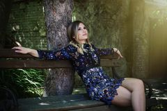 Beautiful girl in short elegant dress sit on wooden bench in fro. Nt old house day shot Royalty Free Stock Photo