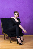 Beautiful girl with short haircut in a chair on a purple background Stock Images