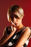 Beautiful girl with short haircut and sporty figure on a red background Royalty Free Stock Photo