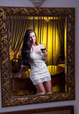 The beautiful girl in a short white dress looking into mirror Stock Photography