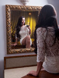 The beautiful girl in a short white dress looking into mirror Royalty Free Stock Image