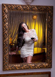 A beautiful girl in a short white dress reflected into a into mirror Stock Images