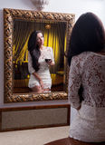 A beautiful girl in a short white dress reflected into a into mirror Royalty Free Stock Photos
